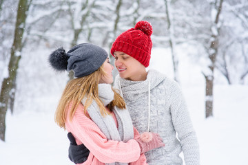 Couple in love looking at each other during snowfall