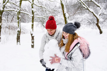 Young couple holding snow ball