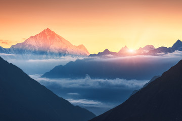 Fototapeten Gebirge Majestic scene of silhouettes of mountains and low clouds at colorful sunrise in Nepal. Landscape with snowy peaks of mountains, beautiful sky and yellow sunlight. Rocks and sun rays.Nature background