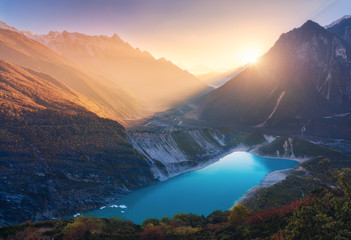Wall Mural - Mountains and lake with blue water at sunset in Nepal. Majestic landscape with high mountains, lake, lightened hills, rocks, yellow sunlight and blue sky. Bright sunny evening. Travel. Nature