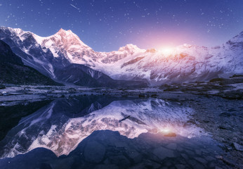 Wall Mural - Night scene with himalayan mountains and mountain lake at starry night in Nepal. Landscape with high rocks with snowy peak and sky with stars and moon reflected in water. Moonrise Beautiful Manaslu