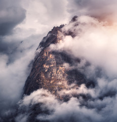 Wall Mural - Majestical mountains in clouds in overcast evening in Nepal. Landscape with beautiful high rocks and dramatic cloudy sky with sunlight at sunset. Nature background. Fairy scene. Amazing mountains