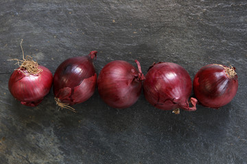 Red onions in a line on dark slate table top