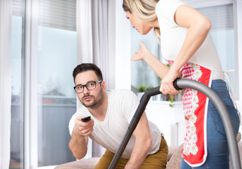 Woman vacuuming while man watching tv