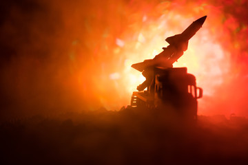 Rocket launch with fire clouds. Battle scene with rocket Missiles with Warhead Aimed at Gloomy Sky at night. Rocket vehicle on War Backgound.