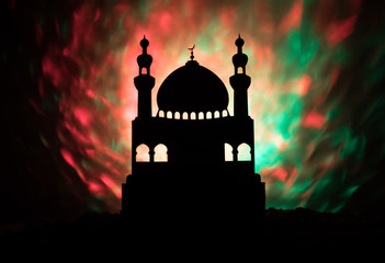 Silhouette of mosque building on toned foggy background. Ramadan Kareem background. Mosque at sunset.
