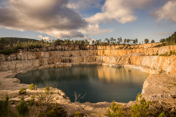 Blue lake in mining industrial crater, acid mine drainage in rock