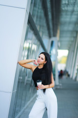 Woman go travel with luggage in Lviv international airport and drink coffee