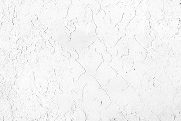 Concrete wall, painted in white, with damaged paint.