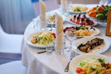 festive table with white tablecloths, glasses for drinks and food in the restaurant at the Banquet for a festive dinner