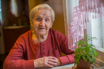 Elderly senior woman sitting at the table.