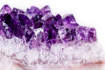 Macro mineral stone purple amethyst in crystals on a white background