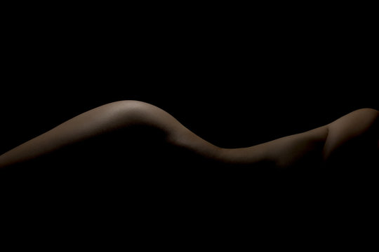 Silhouette of a body part , nude woman isolated on black background