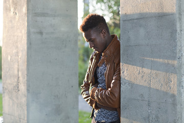 Handsome young black man leaning on a wall looking down
