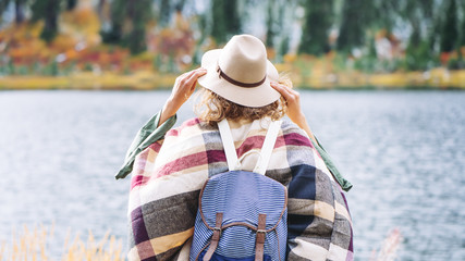 Woman traveling among mountains, forest and lake wearing backpack, hat and poncho, boho and wanderlust style