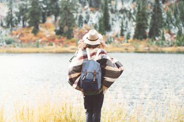 Woman traveling among autumn mountains, forest and lake wearing backpack, hat and poncho, boho and wanderlust style