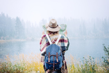 Travel woman reading map among amazing  wilderness, enjoy the nature landsape. Forest and lake, wearing hat and poncho, boho and wanderlust style