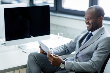 smiling african american businessman reading newspaper at workplace