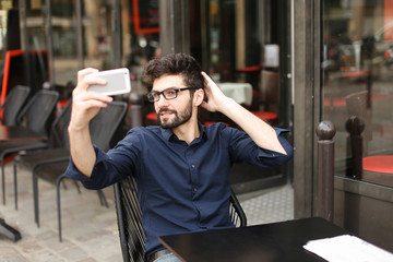 Happy businessman typing message to partner and wondering with successful surprise in . Handsome male person dressed in classic style blue shirt and grey jeans sitting at street cafe near glasses and