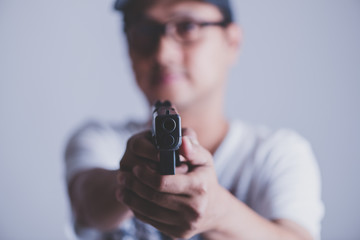 young man asian holding a gun aiming at the gun, with selective focus