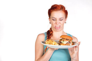 young woman looks disgusted at  plate with  hamburger