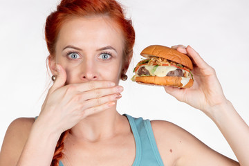 young woman covers her mouth with her hand and holds a hamburger