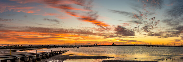 An early evening view of St Kilda Pier against a dramatic red sunset in Melbourne, Victoria, Australia