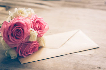 A bouquet of fresh roses and a letter on a wooden background. Vintage. Selective focus. Copy space. Toning