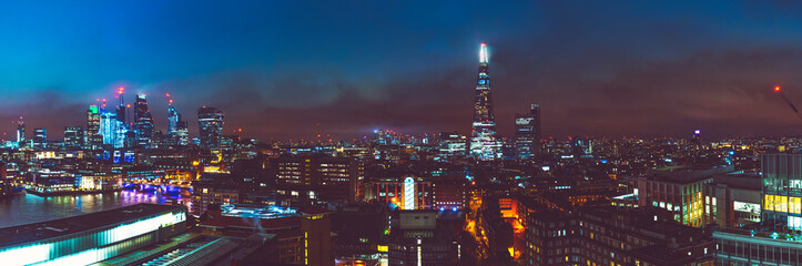 big panorama picture of london cityscape at night with thames river and shard