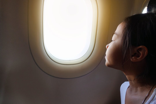 Asian child girl is sitting and looking outside the window of the plane interested.