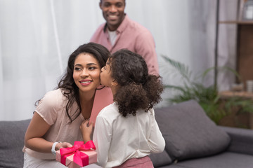 african american daughter kissing mother and presenting gifts to her on mothers day