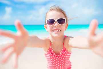 Portrait of happy little girl at tropical beach on exotic island