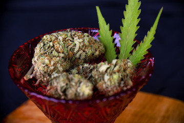 Dried cannabis nugs (sour tangie strain) on a red glass with a pot leaf over black background