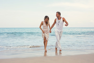 Cheeful couple in summer clothes on the beach