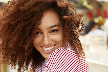 Glad cheerful African American female model with frizzy dark bushy hair, being in high spirit after hearing good news or recieving compliment from boyfriend, poses at camera with gentle smile. Wall mural