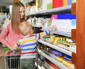 Young mother with little son choosing baby food in supermarket