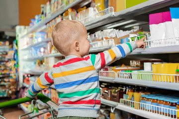 Cute little boy in shopping cart choosing baby food at supermarket