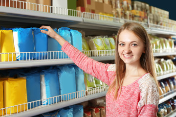 Young woman choosing baby food in supermarket