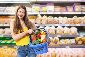 Young woman with basket shopping in supermarket
