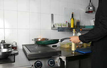 Chef flambeing vegetables in restaurant kitchen