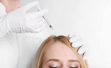 Young woman with hair problem receiving injection on light background, closeup