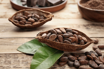 Half of cocoa pod with beans on wooden table