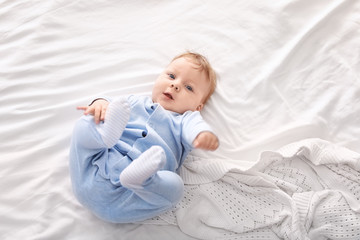 Cute little baby lying on bed, top view
