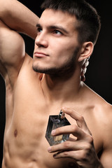 Handsome man with bottle of perfume on dark background