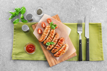 Wooden board with delicious grilled sausages and sauce on table