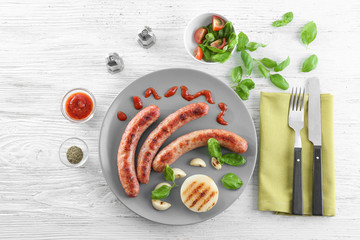 Plate with delicious grilled sausages on wooden background