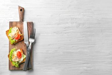 Wooden board with tasty chicken bruschettas on table
