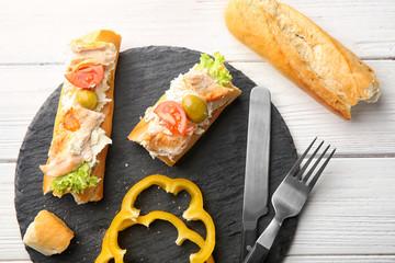 Slate plate with tasty chicken bruschettas on wooden table