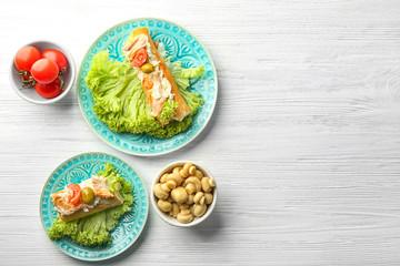 Plates with tasty chicken bruschettas on wooden table