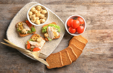 Plate with tasty chicken bruschettas and ingredients on wooden table